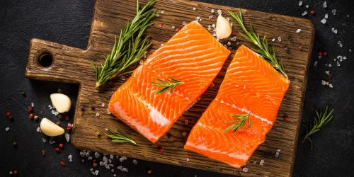 Fresh fish. Raw salmon fillet at wooden cutting board with ingredients for cooking. Top view at black table.